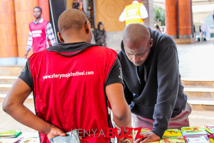 A storymoja official assists a guest while he is buying a book